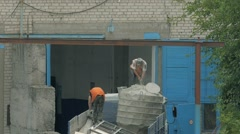 Man mixes cement in a large capacity. A container of cement is in body truck Stock Footage
