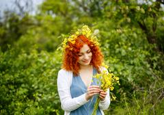Girl weaves a wreath of wildflowers. - stock photo