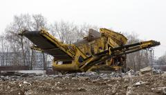 Stone crusher parked by the construction site Stock Photos