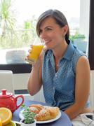 Cheerful woman having a continental breakfast - stock photo