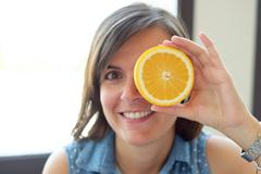 Woman joking with a slice of orange - stock photo