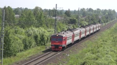 Grey-and-red RZD suburban train gains speed from the station Stock Footage
