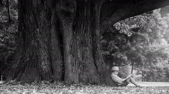 Black and white video: a boy sits at the foot of the huge tree reading a book Stock Footage