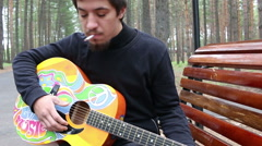 Young man and guitar in hippie style and man smokes a cigarette in the forest Stock Footage