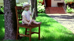 Baby sitting on the chair in the garden and using tablet  Stock Footage