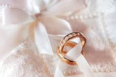 Golden wedding rings with diamonds on fabric. Wedding jewelry details. Engage - stock photo
