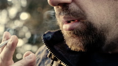 A man smoking in the park: nervously smoking, thoughtful, impatient, lonely  Stock Footage
