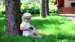 Baby sitting on the grass in the garden and using tablet  Stock Footage