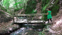 Attractive girl walk over forest wooden bridge above summer spring with ecolo Stock Footage