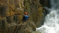 Adventurous tourist rappels into the river beneath Datanla Falls near Da Lat Stock Footage