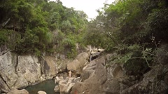 Tourists clamber over boulders in river-carved canyon near Nha Trang, Vietnam - stock footage