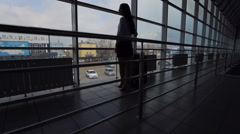 A woman stands inside airport building have glass walls Stock Footage
