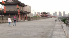 People walk by the Great Wall in Xian, China. Stock Footage