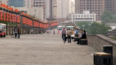 People walk and ride bicycles by the Great Wall in Xian, China. Stock Footage