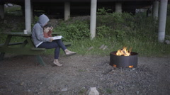 Woman and child reading stories near fire camp site Stock Footage
