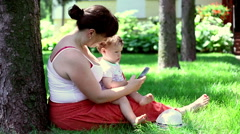 Mother using phone with son Stock Footage