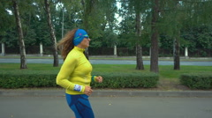 Woman running for better fitness in the city park - stock footage