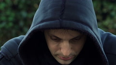 mysterious man with hood smiles devilishly at the camera - stock footage