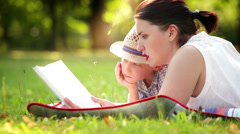 A son with his mum lying in the park on the cover reading a book Stock Footage