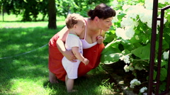 Mother teach how to smell flowers - stock footage