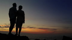 Couple stands on the outcrop watching sunset and kiss Stock Footage