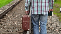 Man with book and suitcase on railway Stock Footage