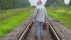 Man with book and suitcase walking away on railway Stock Footage