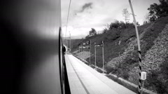 Black and white footage: fast going train enters the tunnel and exits it Stock Footage