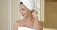 Woman wrapped in towel smiles at camera Stock Footage