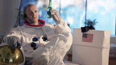 4K Astronaut relaxing in apartment, watching TV & drinking a beer. Stock Footage