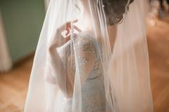 One young slim bride dressing in lace wedding dress preparing for ceremony Stock Photos