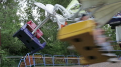 Two children ride on the carousel in an amusement park Stock Footage
