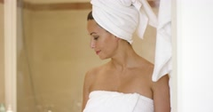 Woman standing at shower stall wrapped in towels Stock Footage