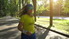 Woman running in city park to lose weight Stock Footage