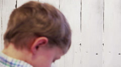 Real-time footage: a boy paints over the fence with white paint Stock Footage