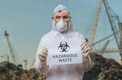 Technician in coverall in landfill warns against dangerous hazardous waste an Stock Photos