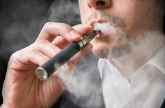 Man is smoking electronic cigarette or vaporizer. - stock photo