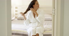 Happy friendly young woman in a white bath robe Stock Footage