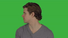 Young guy turns to camera with serious look (Green Key) - stock footage