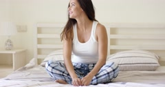 Woman in plaid pajamas sitting on bed Stock Footage