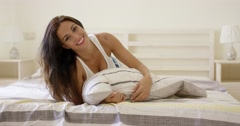 Woman with cheerful expression laying down on bed Stock Footage