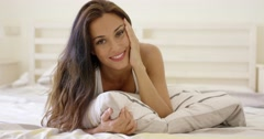 Happy young woman cuddling up in bed Stock Footage