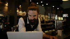 4K Bar owner working on laptop with female employee working in background Stock Footage
