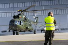 Man in military uniform stands in front of polish Mi-8T helicopter Kuvituskuvat