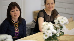 Two women discuss project designer for behind wooden table with flowers Stock Footage