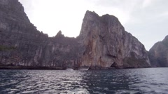 Traditional Longtail Boat Cruising beneath the Limstone Cliffs of Thailand Stock Footage
