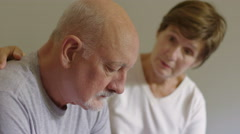 Older woman caring for unhappy man Stock Footage