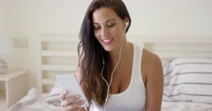 Laughing woman using device with ear buds in bed Stock Footage