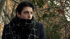 Sad young man with coat and scarf in a city street with yellowed trees Stock Footage