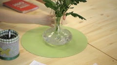 Female hand moves a vase of flowers and glassware still life Stock Footage